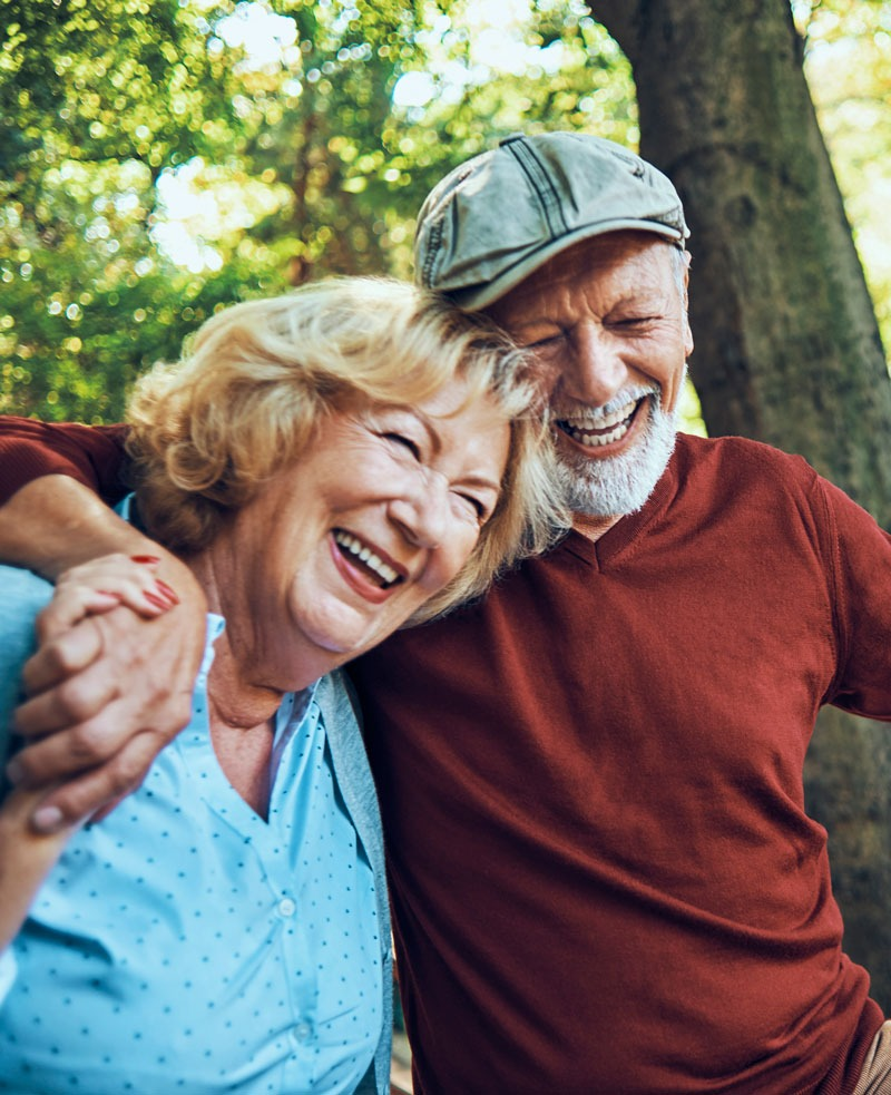 Couple hugging, walking with trees in the background, smiling and laughing