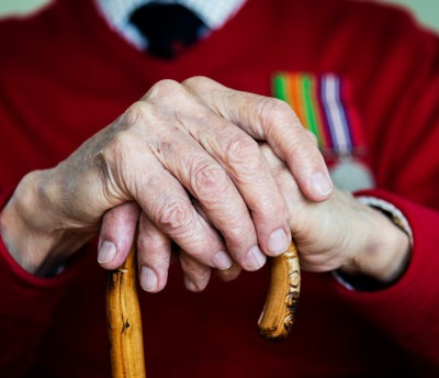 Hands of veteran with cane