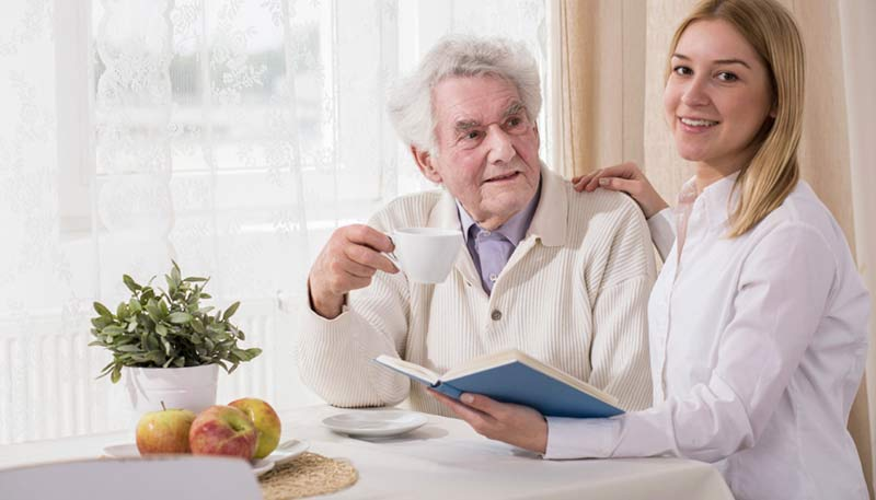older man sitting at table working on advanced care planning with medical professional